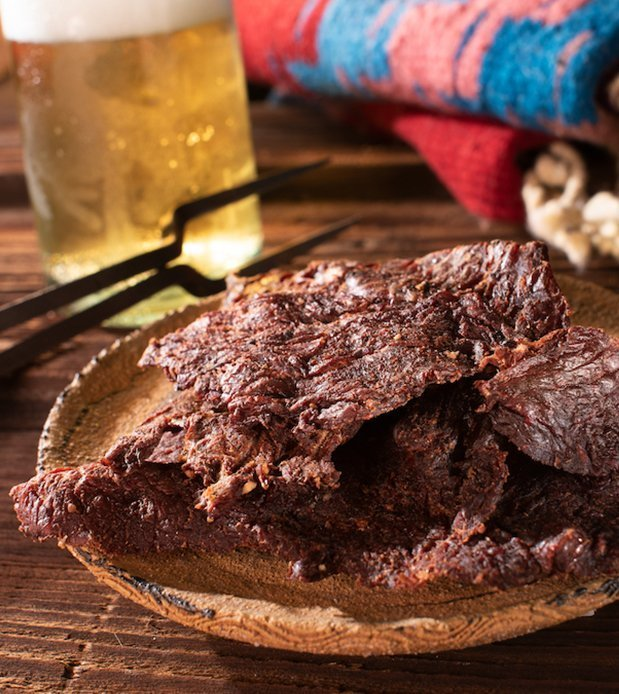 Cowboy jerky on serving plate, with bbq tools and cold beer in background