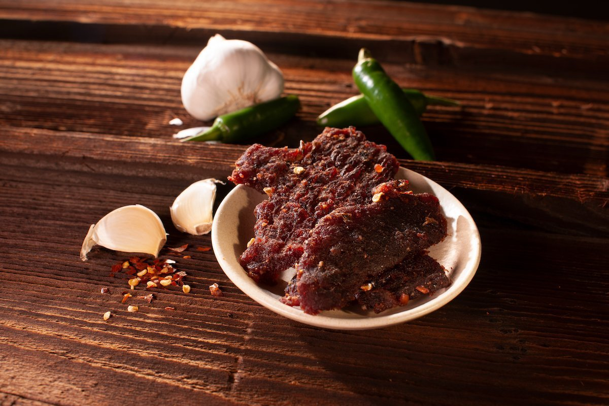 Garlic Jalapeno Beef Jerky plated on wooden table, with decorative garlic and peppers