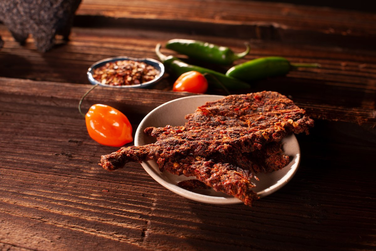 Ring of fire beef jerky in a bowl on top of a wooden table surrounded by peppers