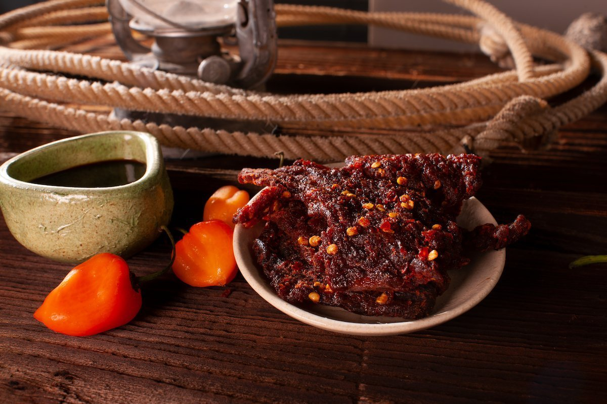 Plated Carolina reaper jerky on a wooden table, surrounded by decorative bowl, peppers, and rope