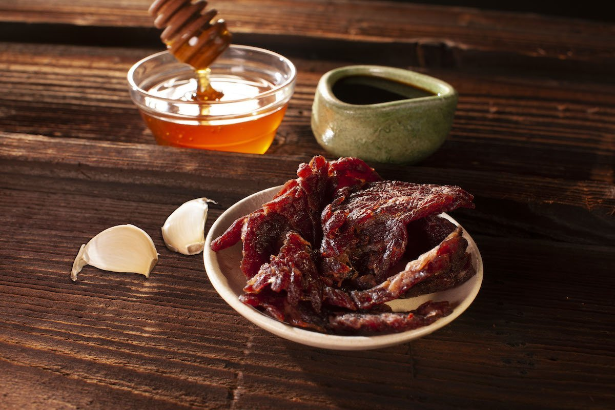 Sweet garlic flavored beef jerky plated and surrounded by decorative bowl, honey, and garlic cloves