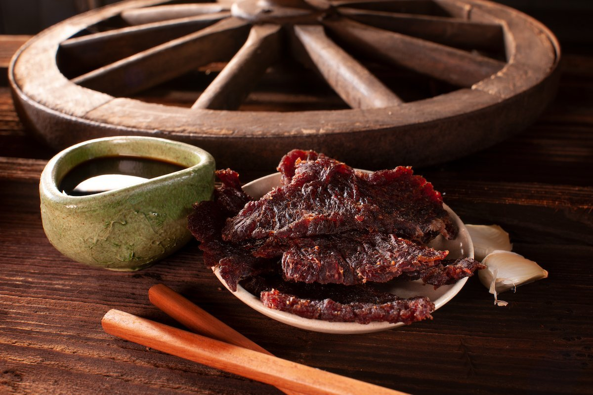 Plated teriyaki beef jerky on wooden table, with decorative bowl, garlic, and wagon wheel