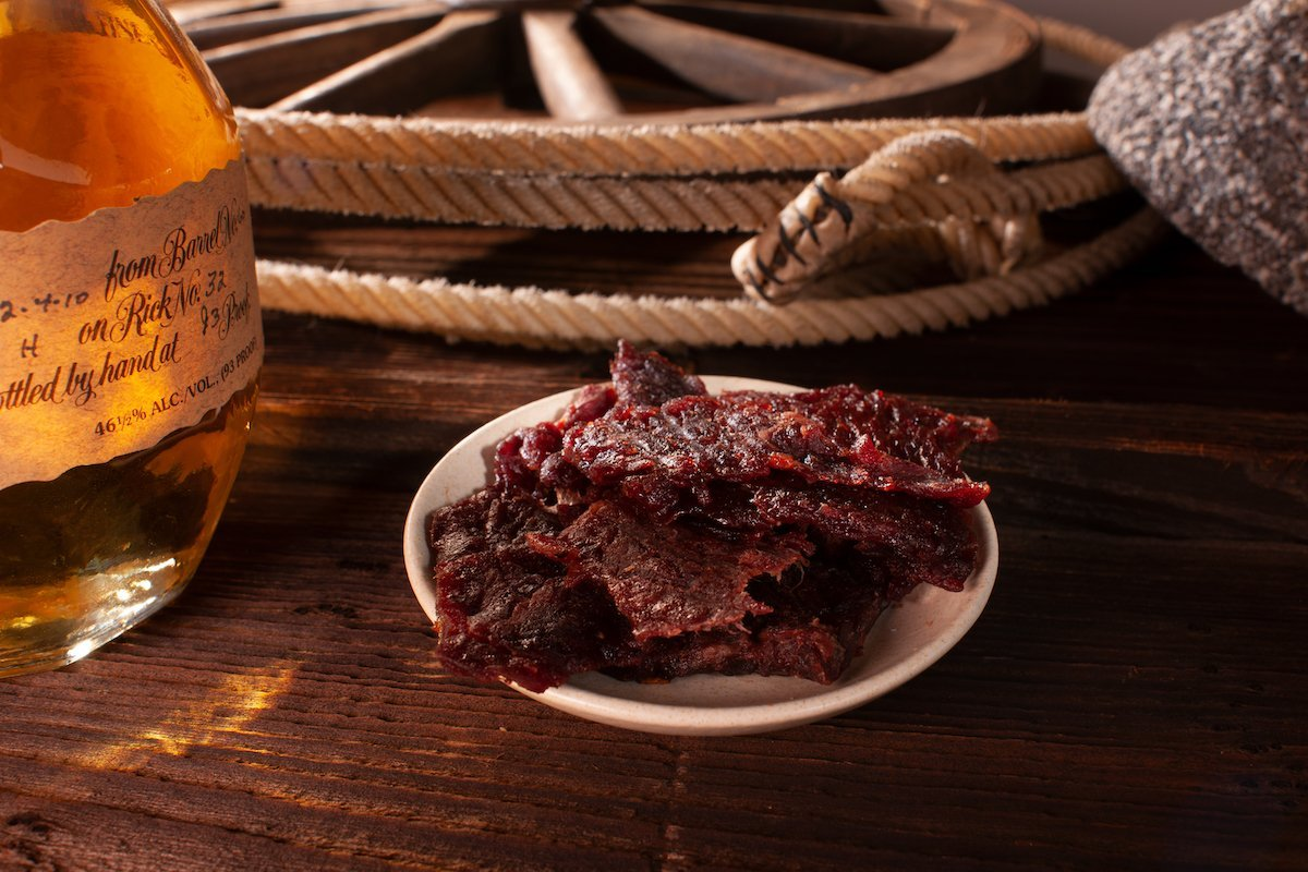 Plated whiskey Scorpion Pepper BBQ beef jerky on wooden table, next to decorative whiskey bottle, rope, and wagon wheel